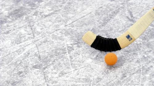 Bild på bandyklubba och en orange bandyboll, på repig is