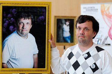Patrik Svedell vid sidan av sin egen tavla i Sällsynta diagnosers tavelutställning