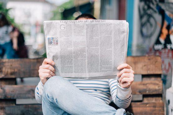 Person som sitter på en bänk läser en nygetstidning